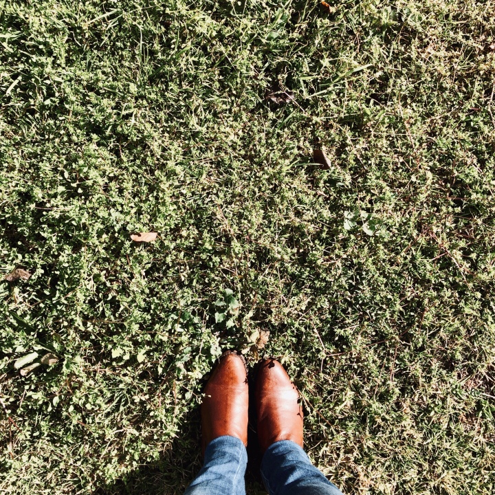 Woman in tan boots standing on green grass.