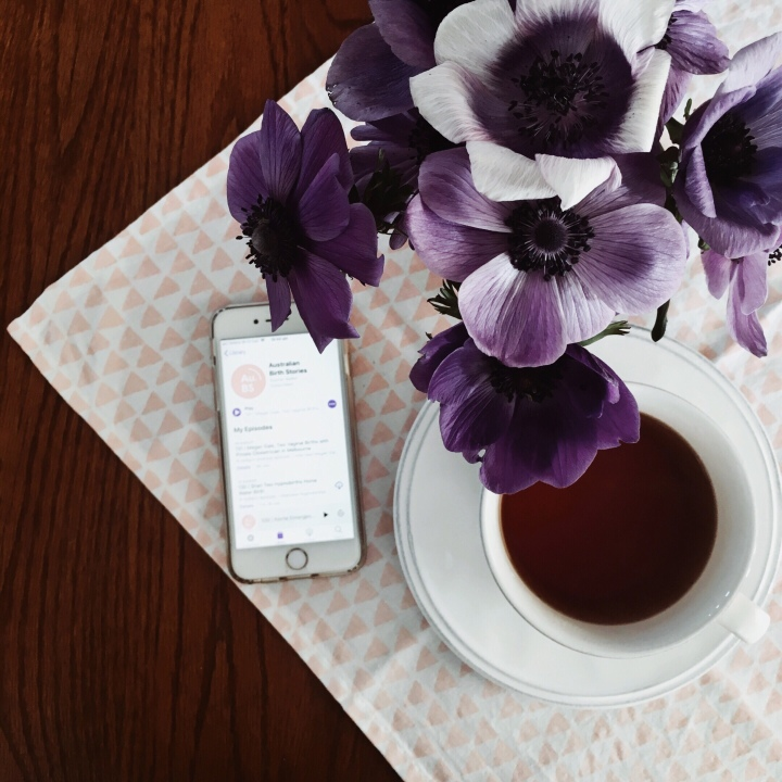 Phone with Australian Birth Stories podcast page sitting beneath purple anemones and beside a cup of tea.