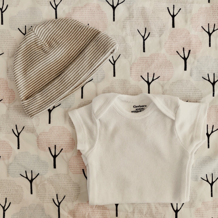 Baby onesie and hat sitting on tree patterned sheets.