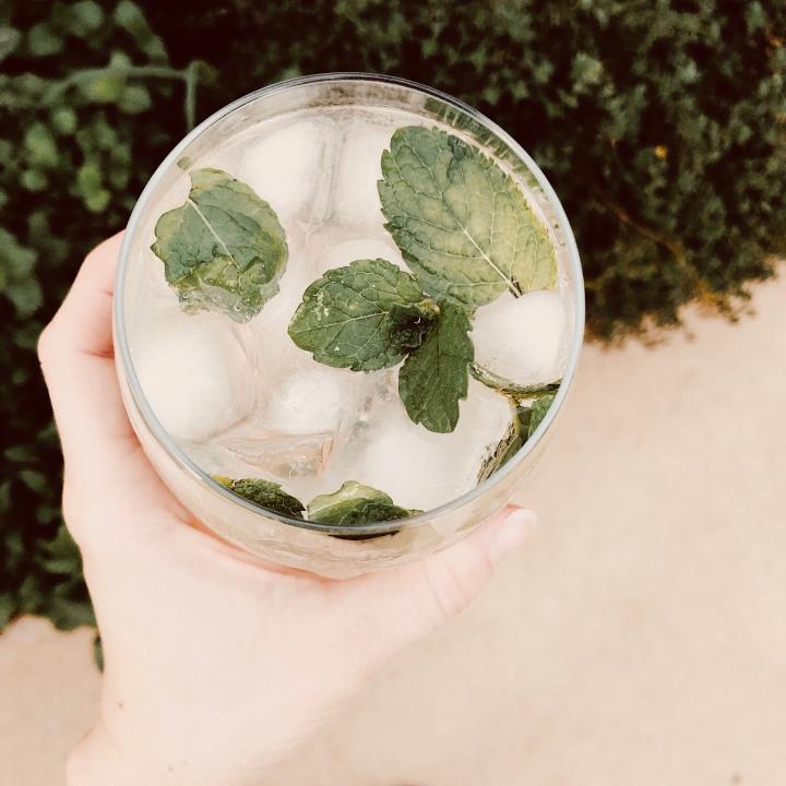 Hand holding glass of elderflower spritz.