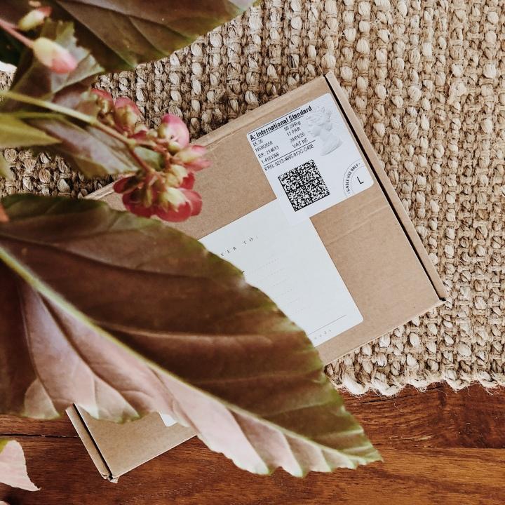 Package underneath vase of greenery.