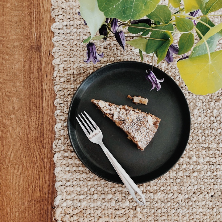A slice of apple cake on a plate beside a vase of Clematis.