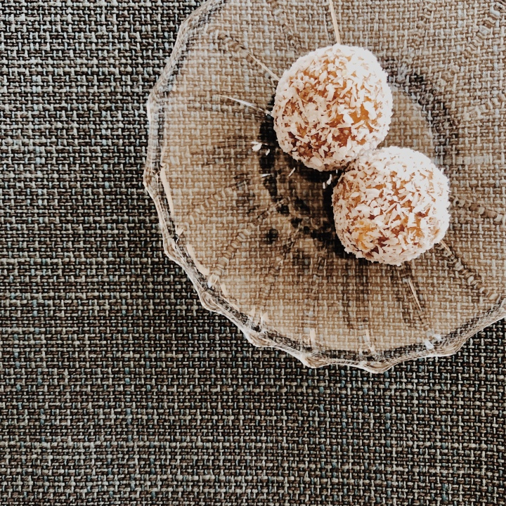 Salted caramel coconut bliss balls on a small glass plate.