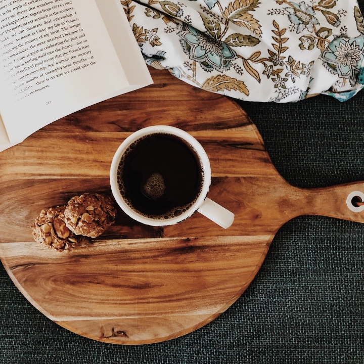 Granola biscuits and tea on wooden board near open book and blue floral blanket.
