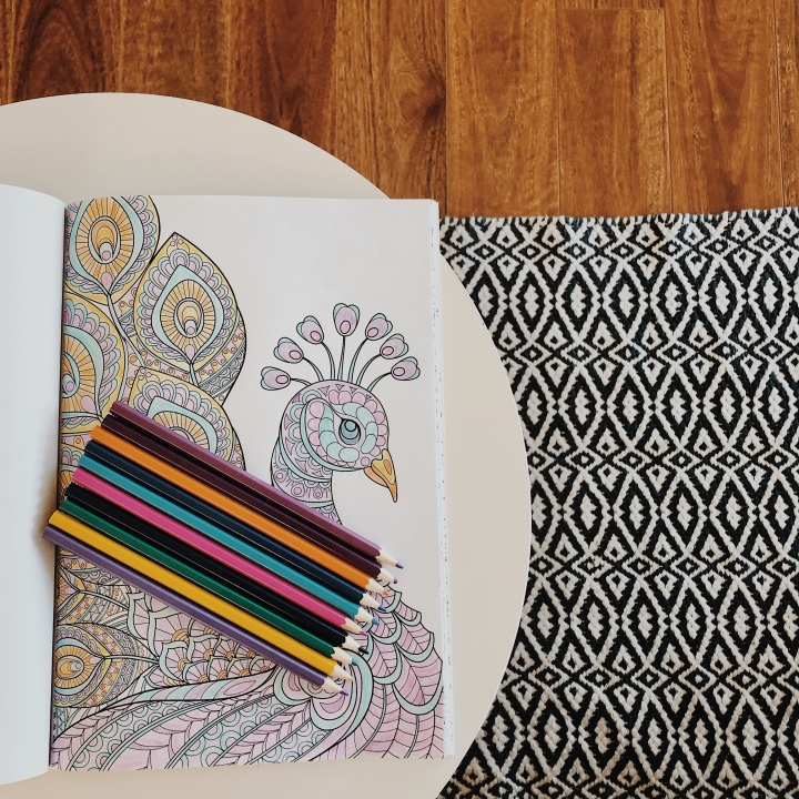 Looking down on a colouring book and pencils.