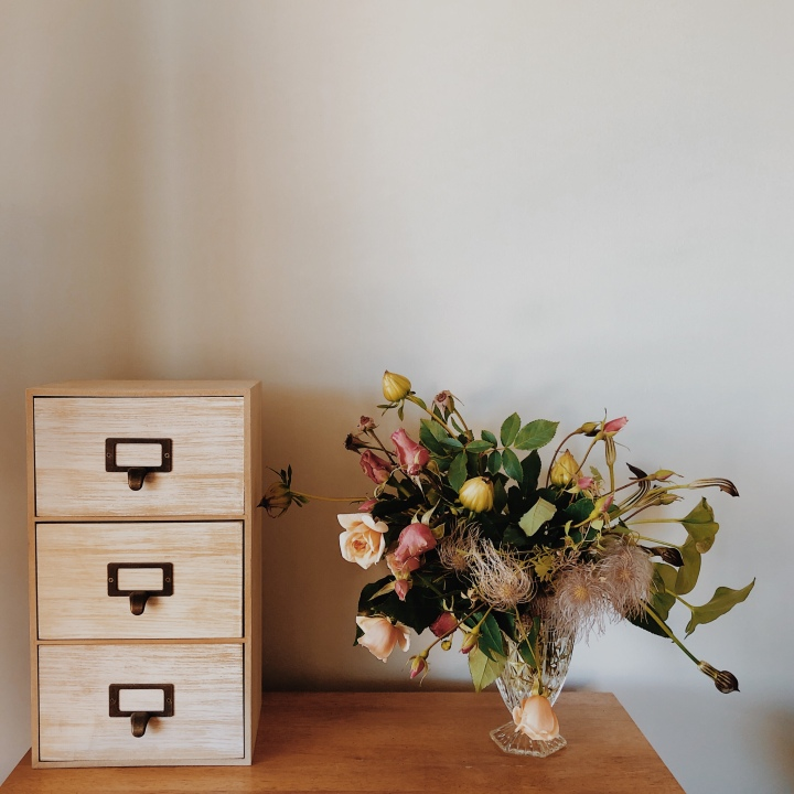 Vase of flowers beside small set of vertical draws.
