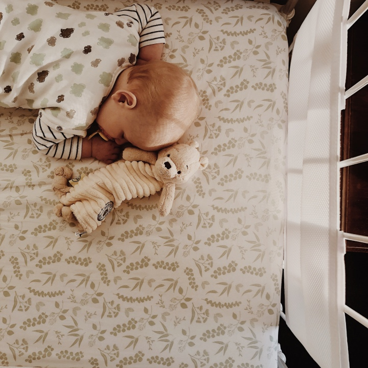 Looking down on a sleeping baby with a toy bear.