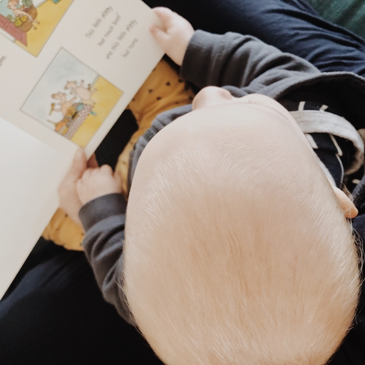 Looking down on a baby boy sitting in his mother's lap, reading a book.