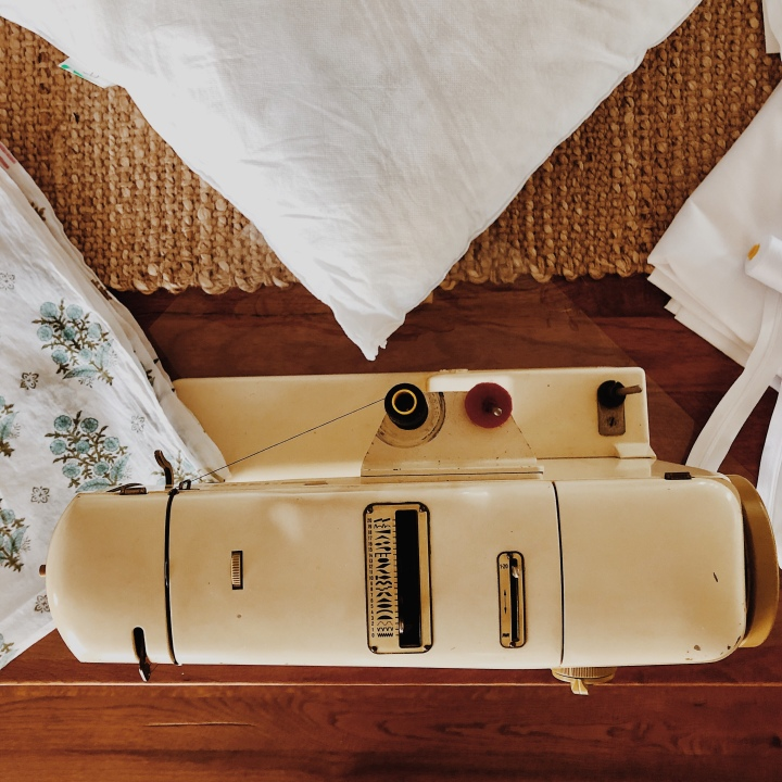 Looking down on a sewing machine surrounded by material, a pillow, zips and cotton.