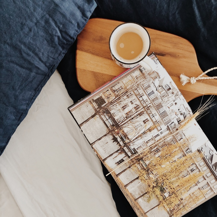 Cup of coffee and open book sitting on a navy blue linen duvet
