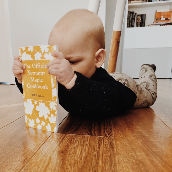 Baby boy playing with a book.