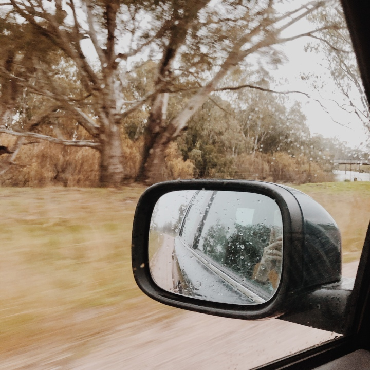 Looking out of a car window at a rainy landscape.