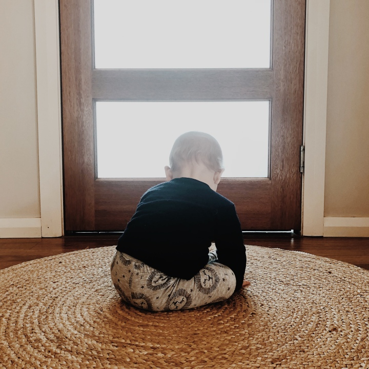 Baby boy sitting on a jute rug in front of door.