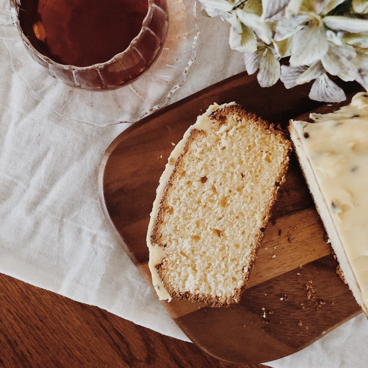 A slice of Madeira cake, alongside a cup of tea and bunch of dried hydrangeas.