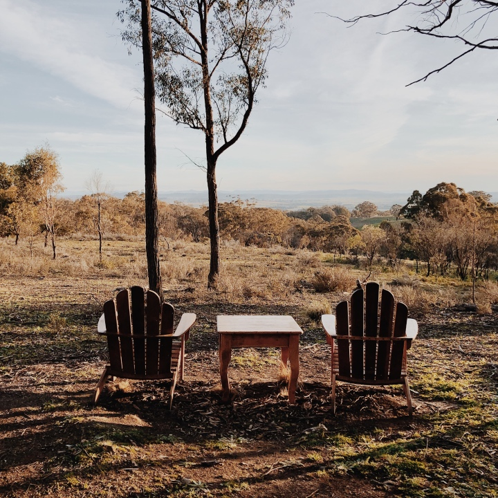 Wooden chairs set up at a lookout at Hillside Airbnb property near Gundaroo, New South Wales, Australia.