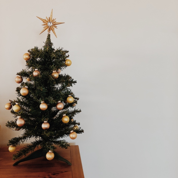 A small Christmas tree decorated with gold and bronze baubles and topped with a gold star.