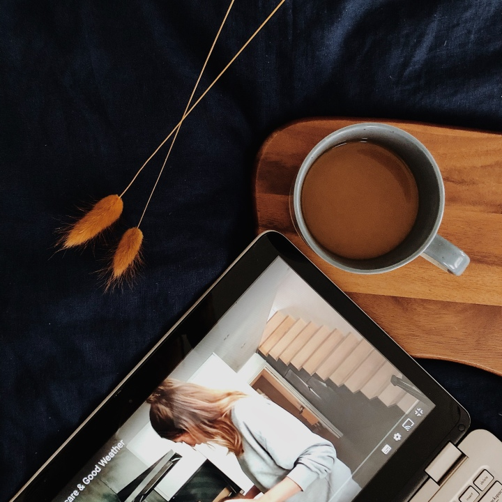 Looking down at a laptop and cup of coffee sitting on a navy blue linen duvet.