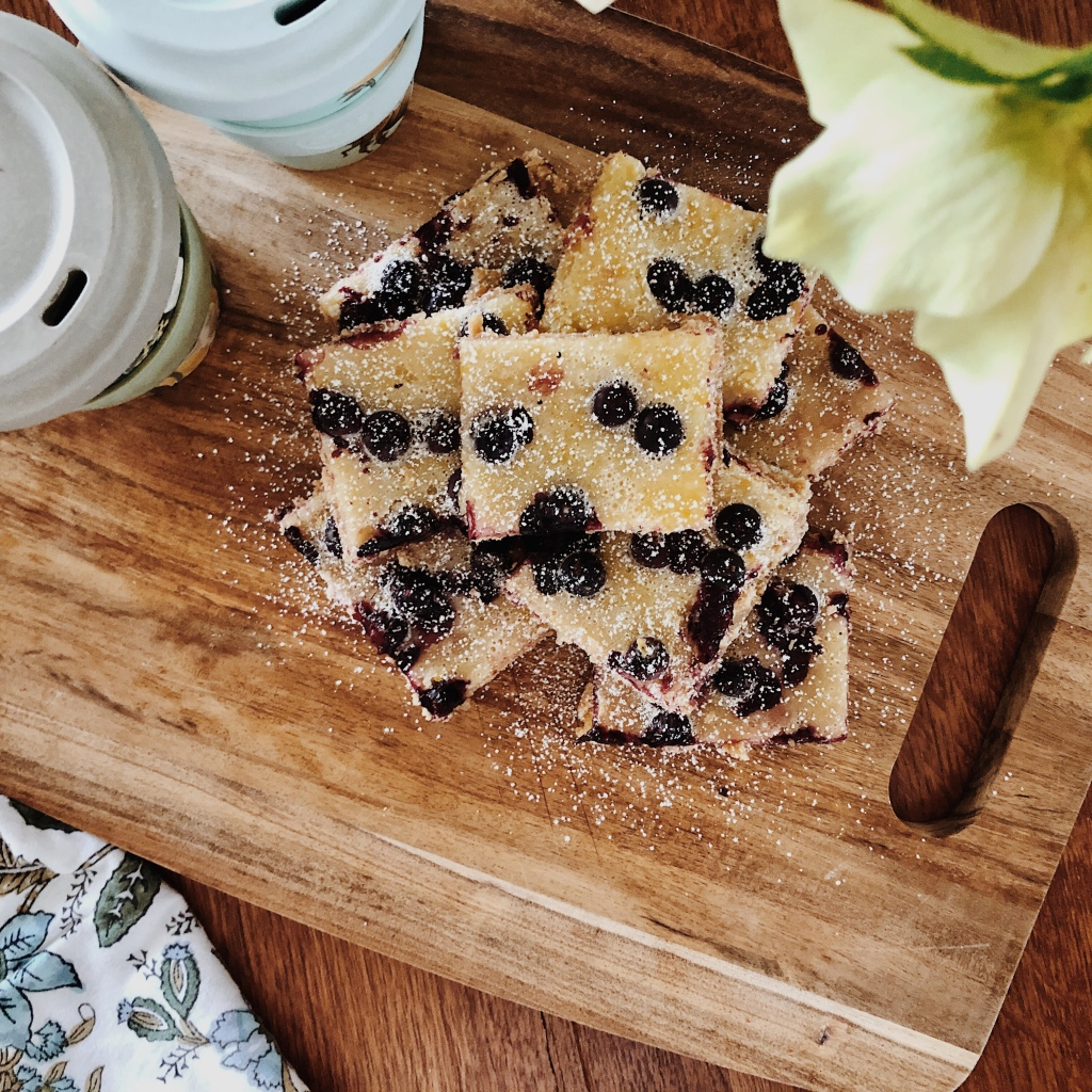 Lemon and blueberry squares dusted with icing sugar sitting on a wooden board, besides two reusable coffee cups and underneath a vase of ellebores.