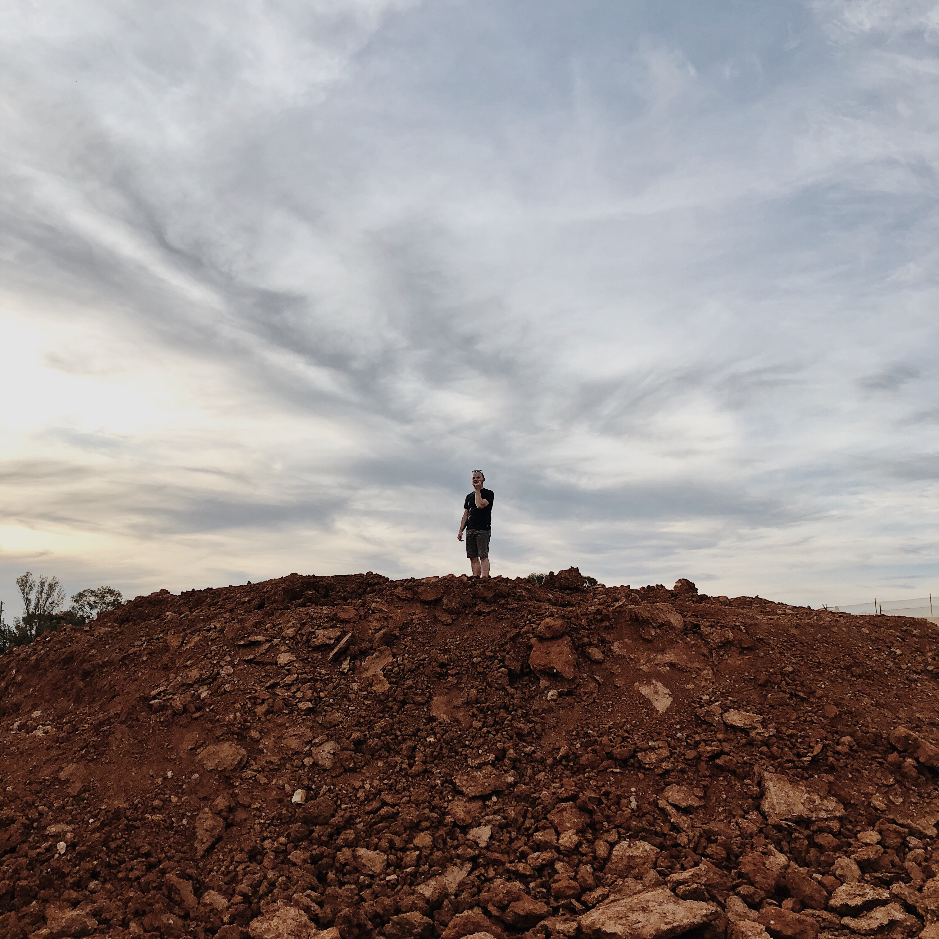 Man standing atop of a pile of dirt.