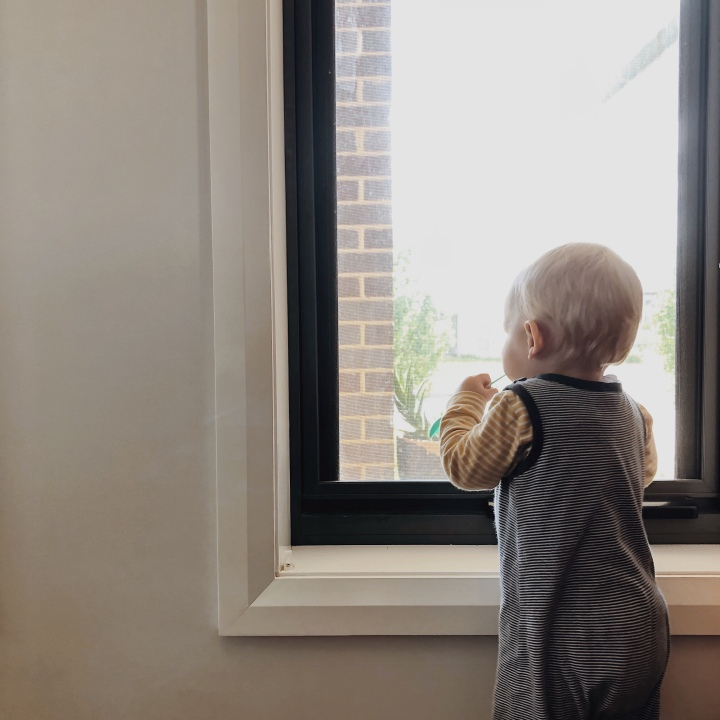 Infant boy staring outside through a window.