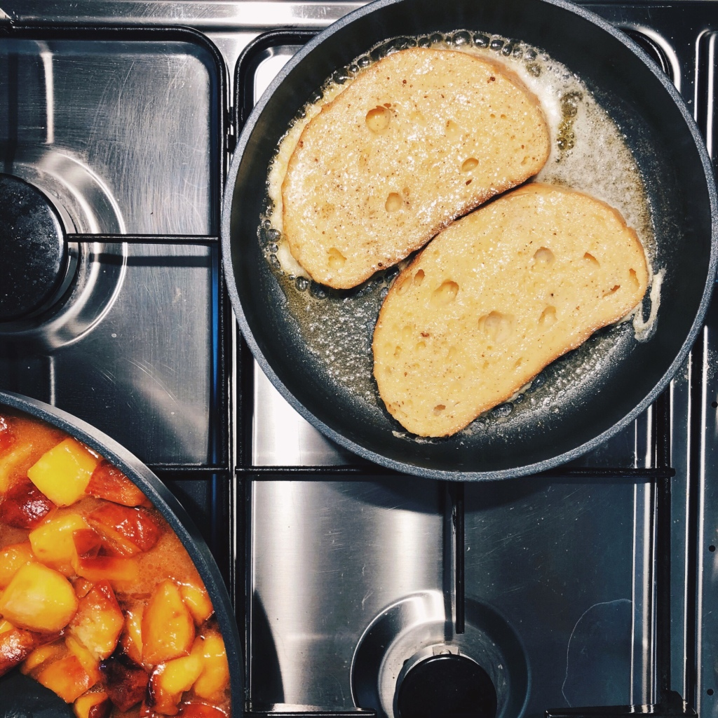 French toast cooking in a pan, beside another pan of caramelised peaches.