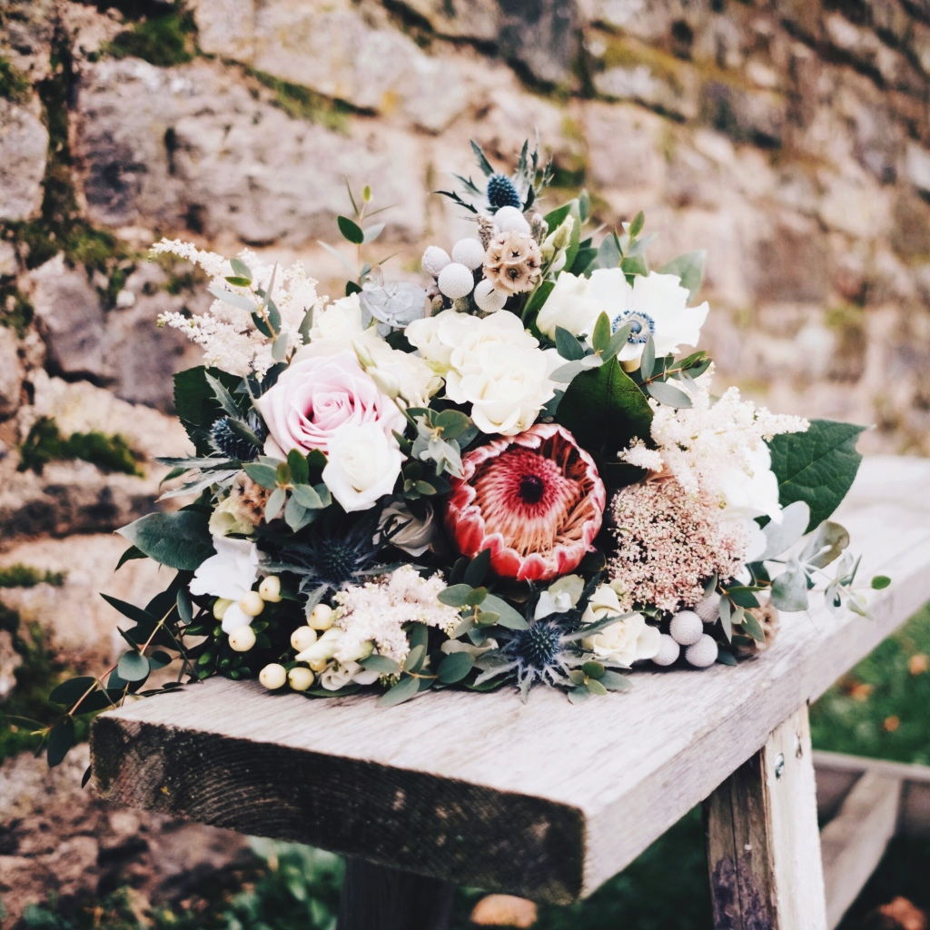 Wedding bouquet on a wooden bench at Lyde Court, Hereford, United Kingdom.