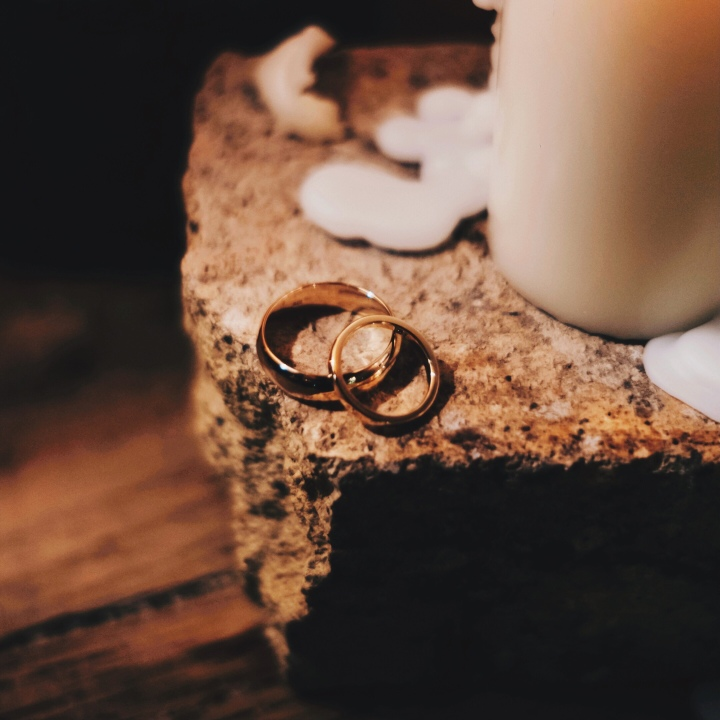 Two gold wedding bands on a piece of rock, besides a dripping candle.