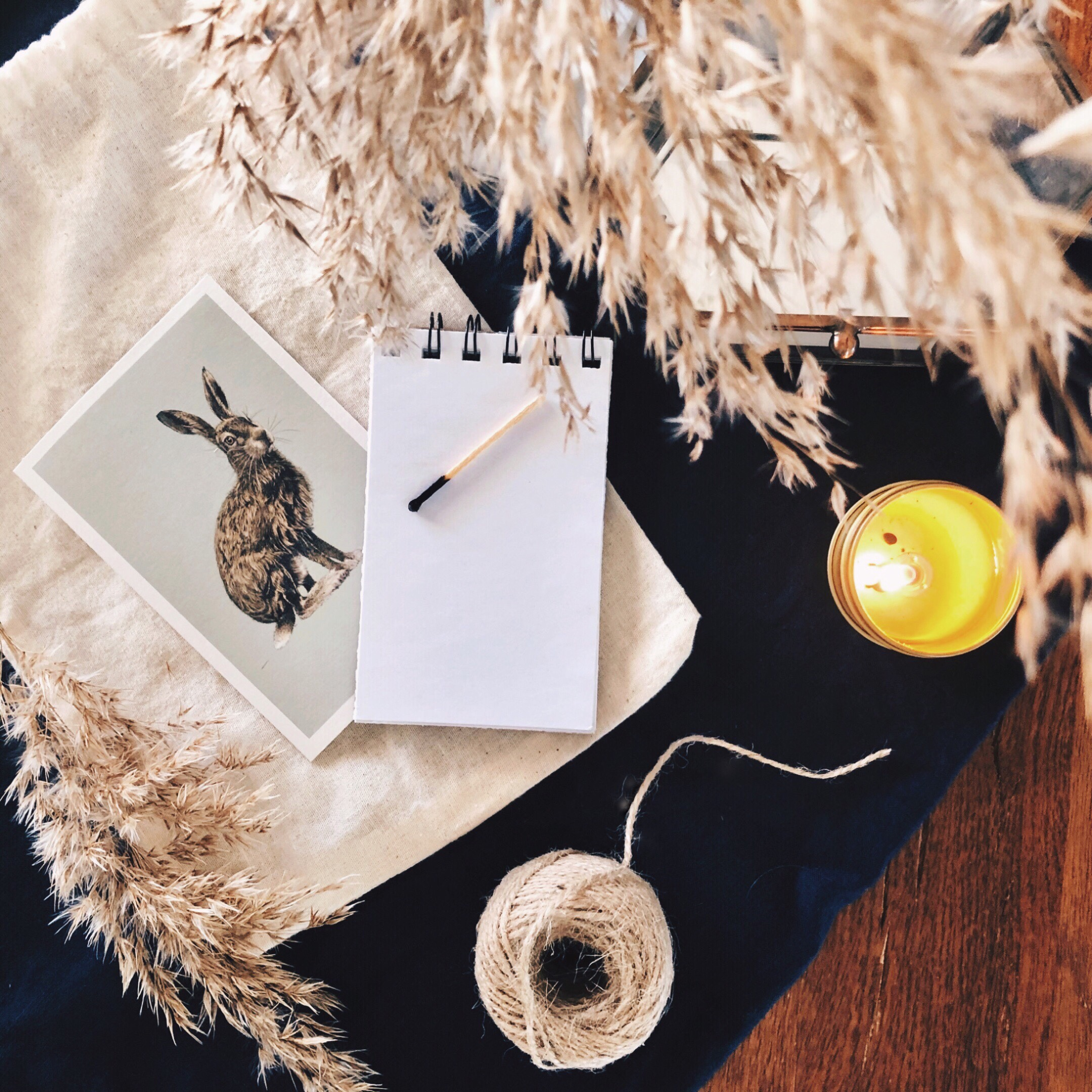 Linen, cotton, dried grasses, a notebook, candle, string and vintage postcard sitting on a timber table.