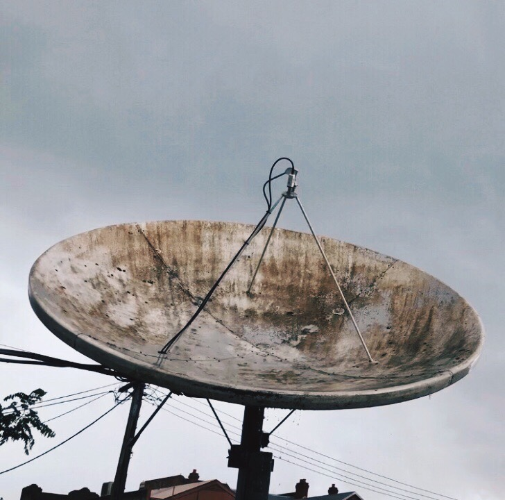 Looking up at a weathered satellite dish set amongst a grey sky.