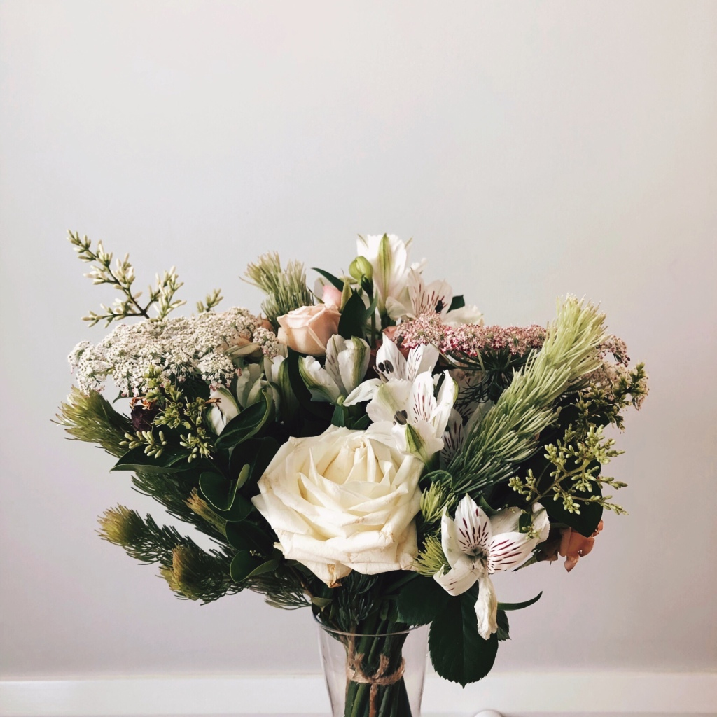 Bunch of white, pink and green flowers set against a light grey wall.