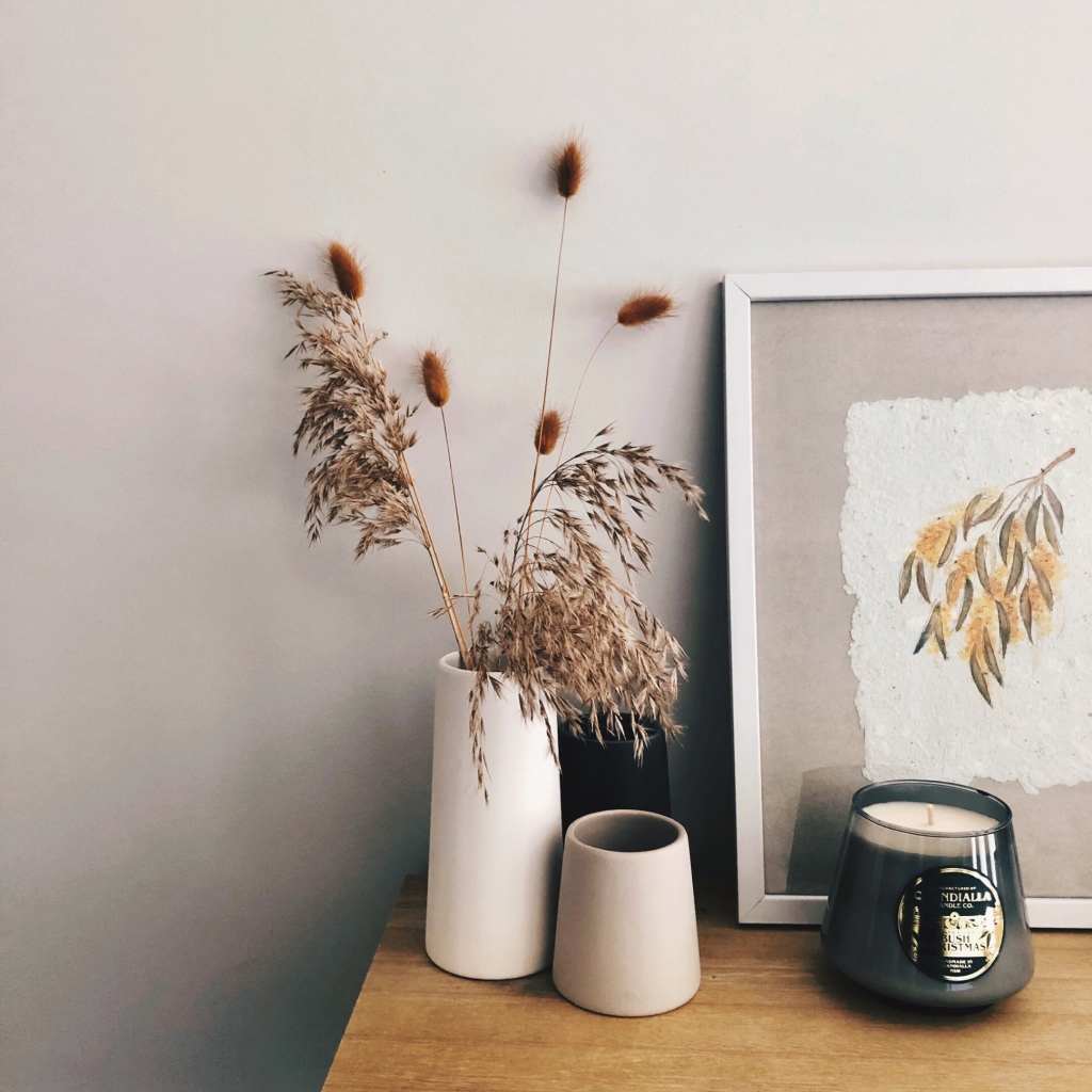 Candle sitting on a table beside vases of dried grasses and a hand painted drawing of wattle.
