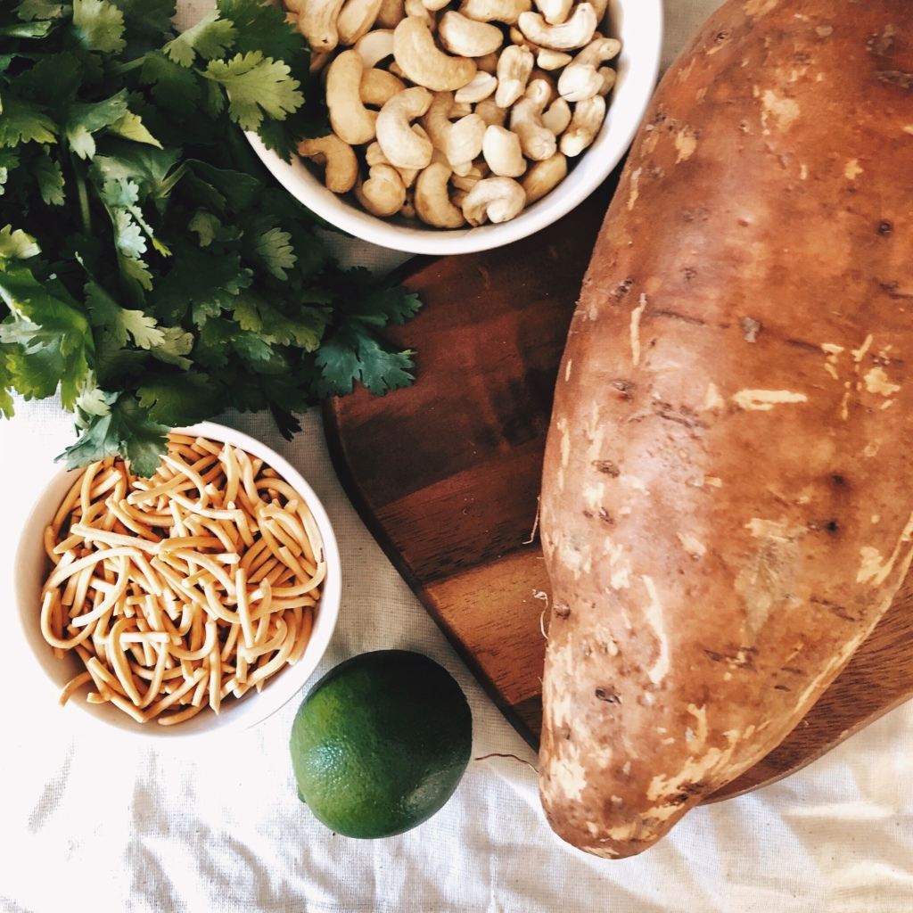 Sweet potato on a wooden board, surrounded by fried noodles, cashews, coriander and a lime.