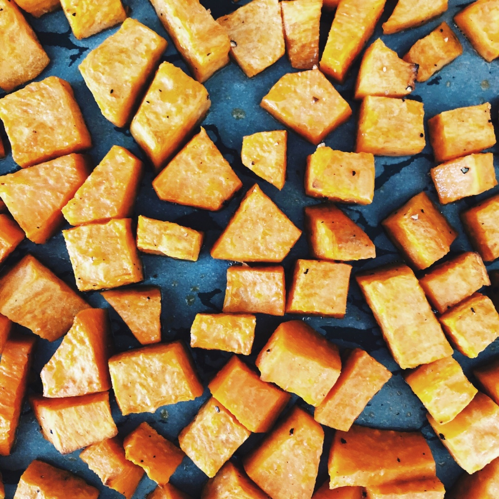 Roasted cubes of sweet potato on a baking tray.