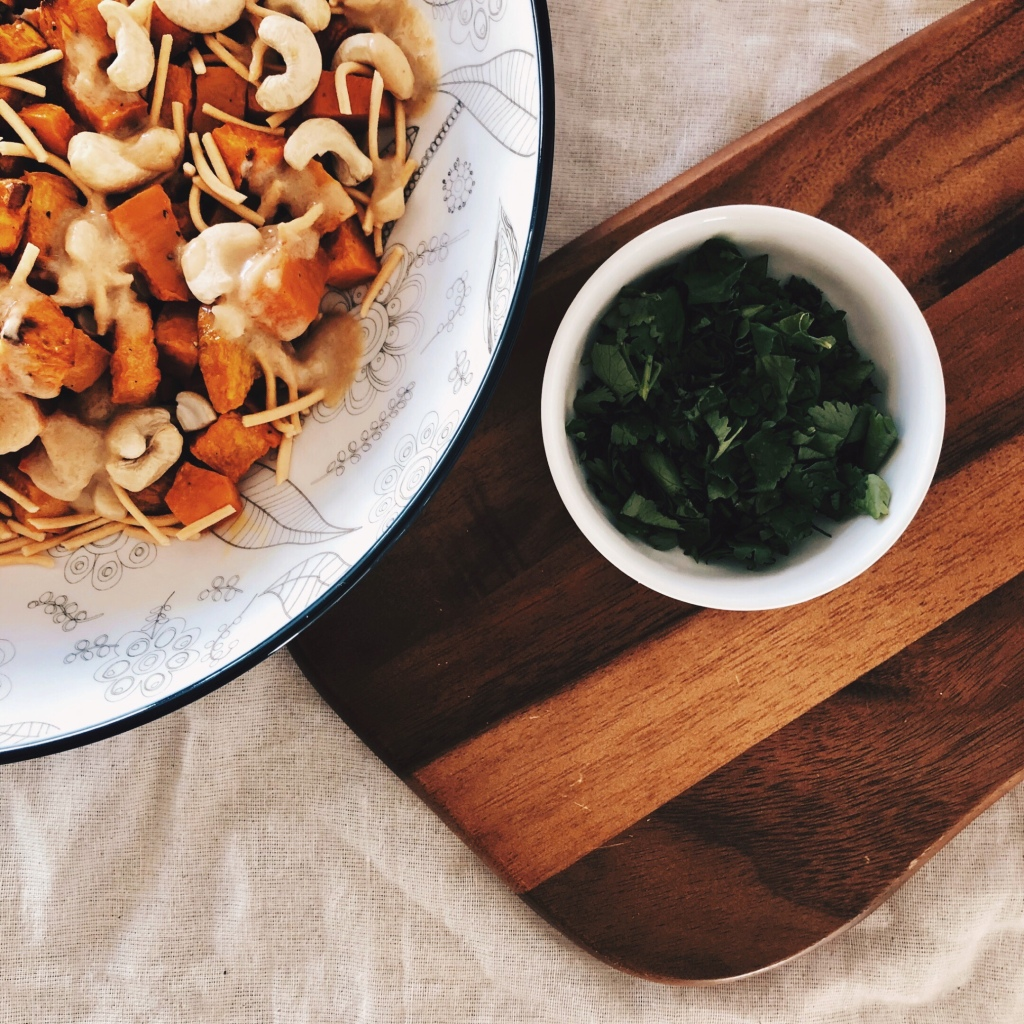 Sweet potato salad in a large bowl, beside a small bowl of chopped coriander, sitting on a wooden chopping board.