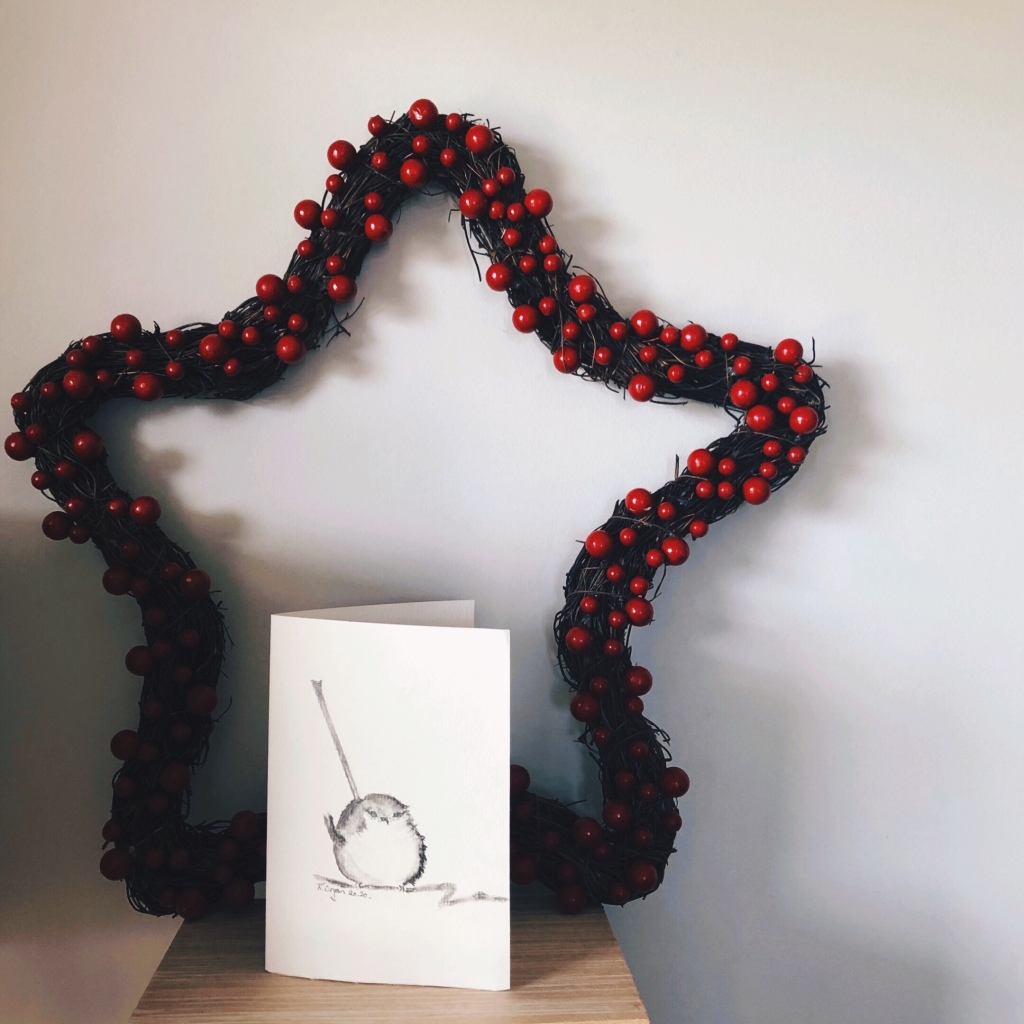 Star shaped Christmas wreath with red berries near a hand drawn picture of a bird.