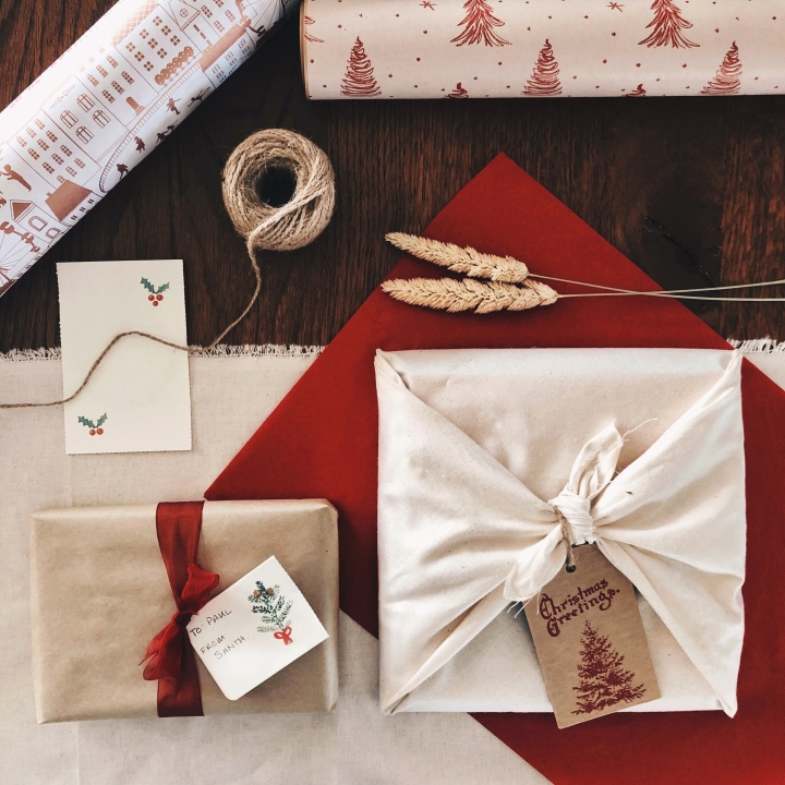 Presents, wrapping paper, calico material, string and gift cards arranged on a wooden table.