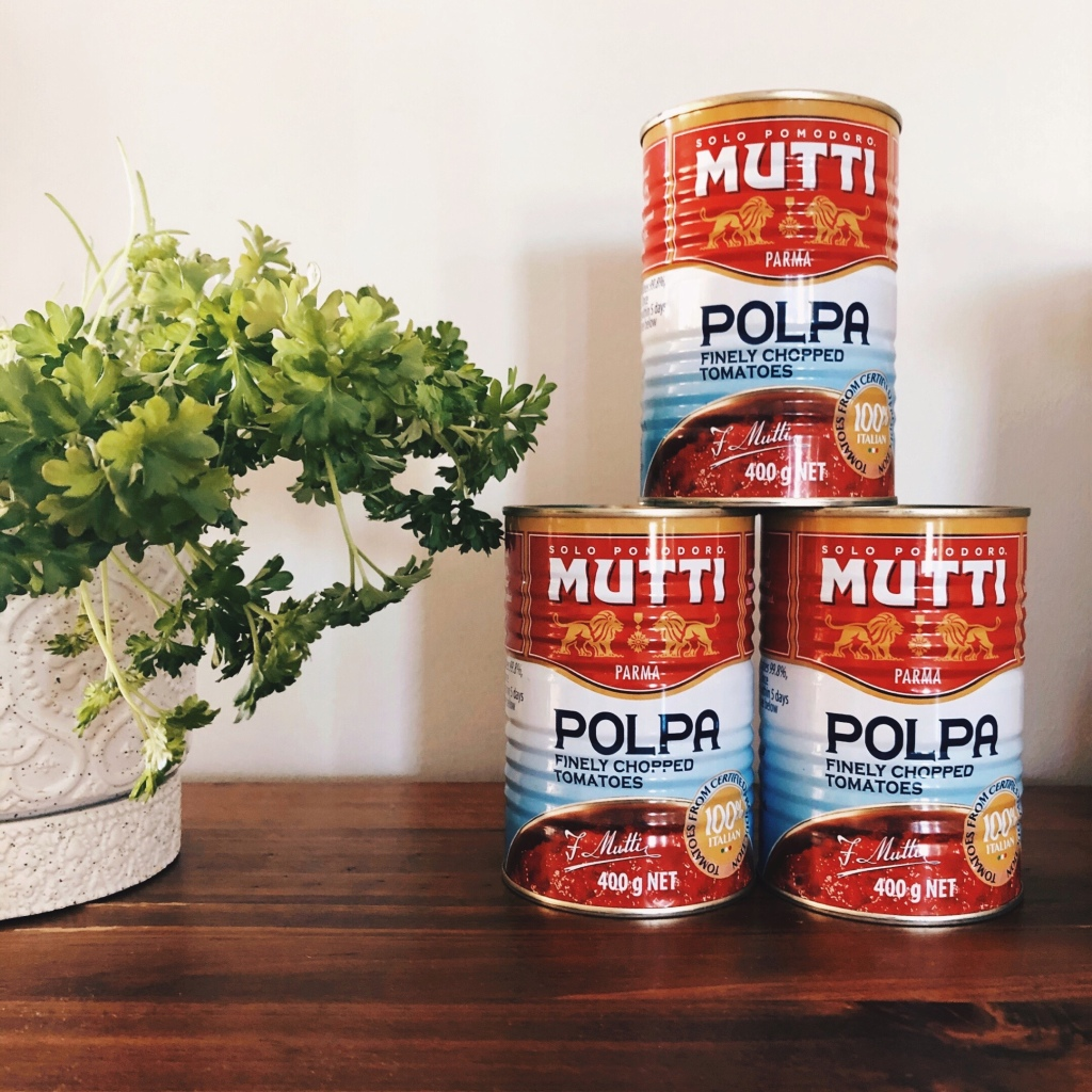 Cans of Mutti Polpa tin tomatoes beside a pot of parsley.