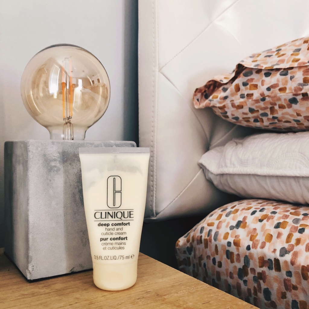 Clinique Deep Comfort Hand and Cuticle Cream in front of a lamp on a table beside a made bed.