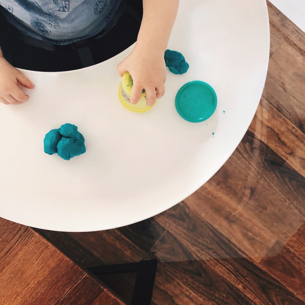 Toddler playing with Play Doh in a highchair.