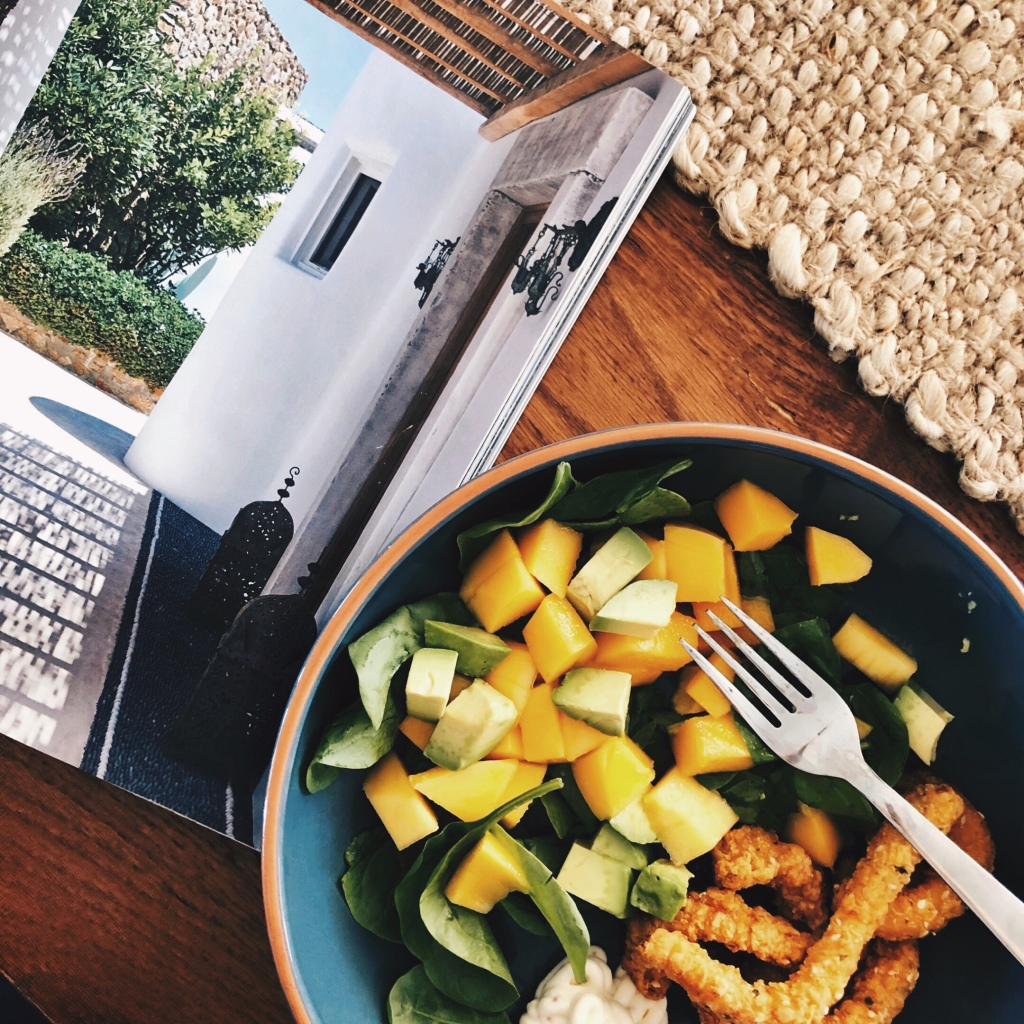 Calamari, spinach, mango and avocado salad beside an open magazine.