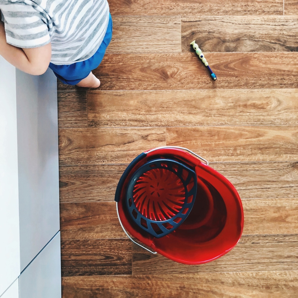 Looking down at a toddler, a toothbrush and a mop bucket on a wooden floor.