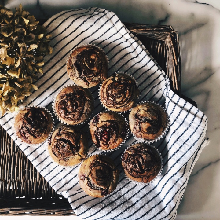 Raspberry and chocolate hazelnut swirl muffins in a rattan tray with a spray of dried hydrangea blooms.
