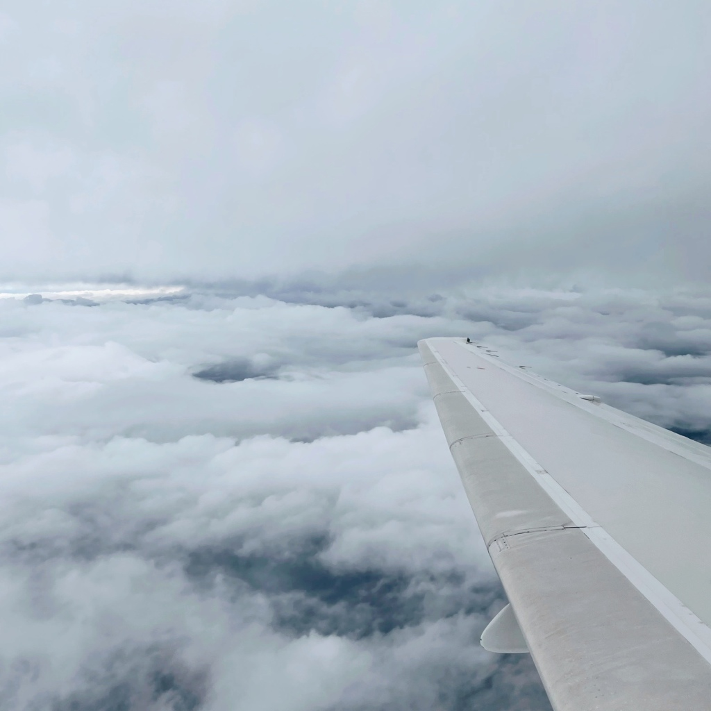 Looking out of plane window onto a cloudy, stormy sky.