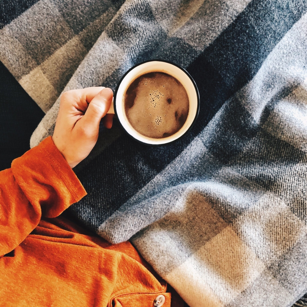 Woman in orange top, holding a mug of hot chocolate underneath a black and white check wool blanket.