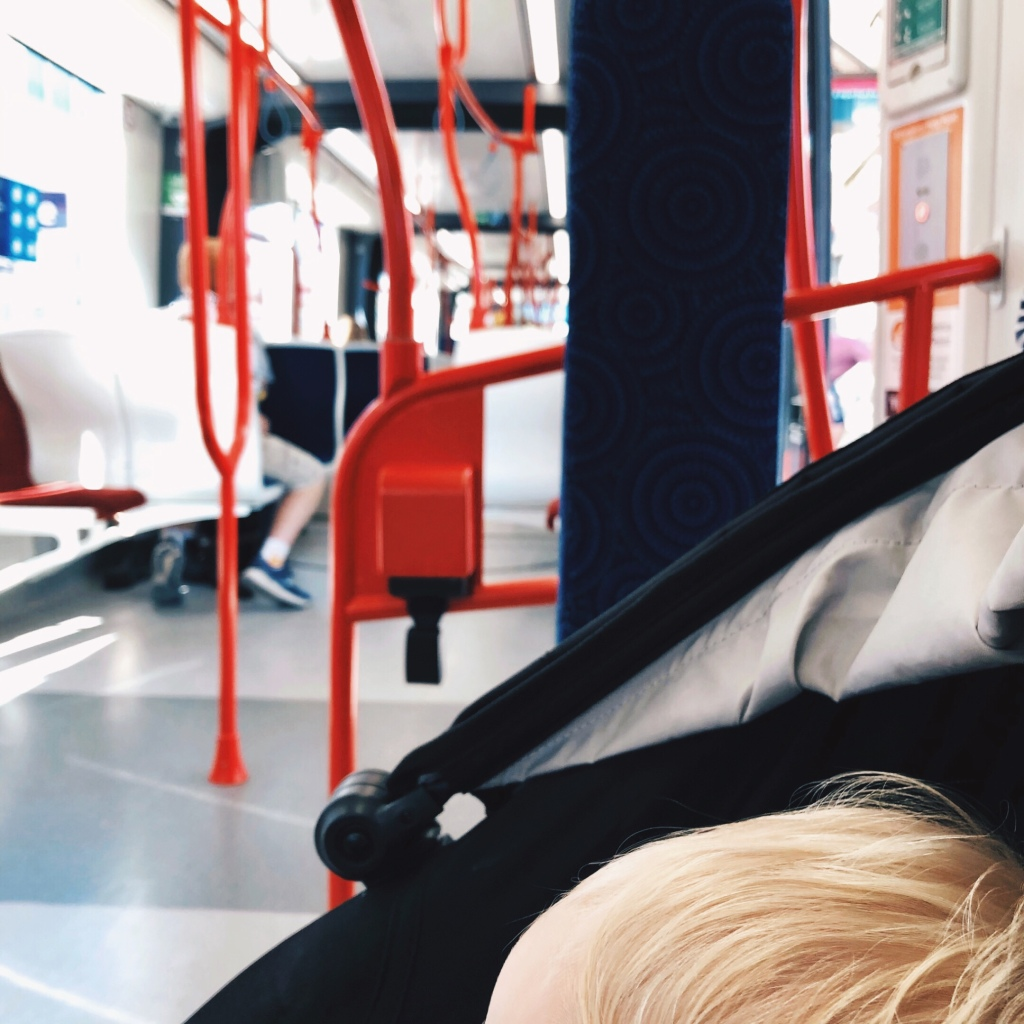 A top of a child's head in a pram with the interior of a tram in the background.
