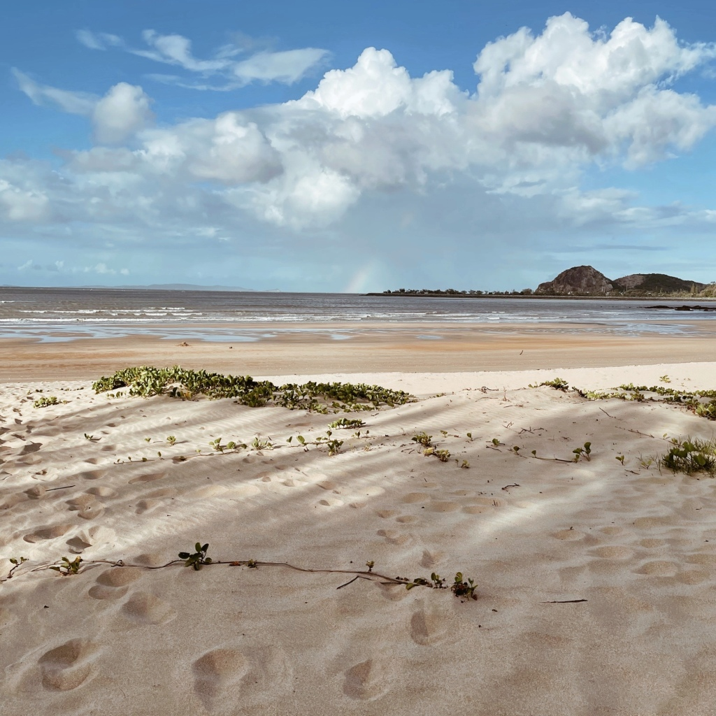 Looking through grassy sand dunes to Farnborough Beach, Yeppoon, Queensland, Australia.