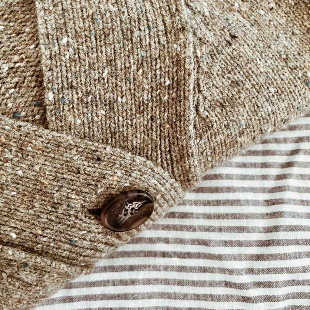 Looking down on an olive, flecked knitted cardigan with tortoiseshell buttons, set upon a grey and white stripe linen sheet.