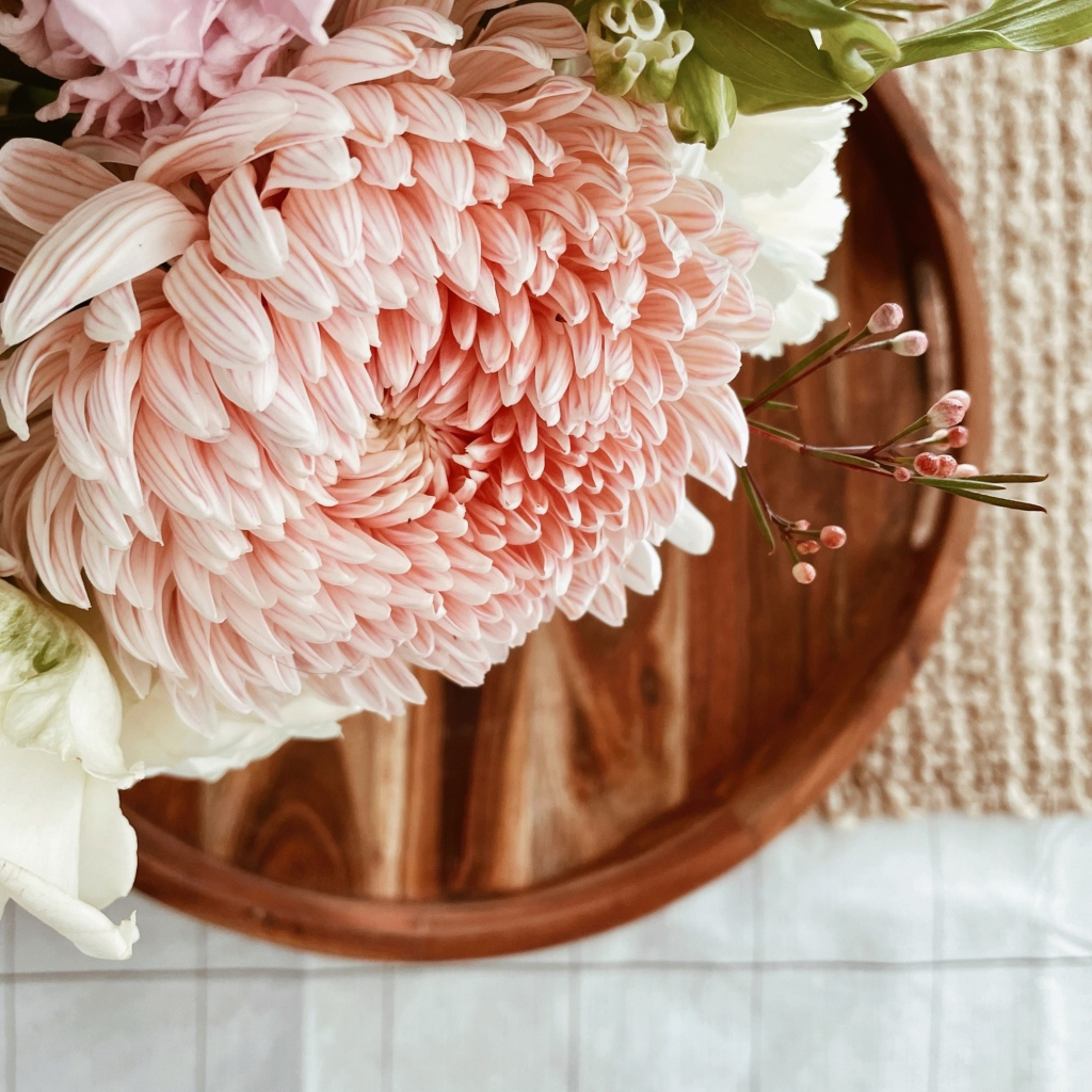 Looking down on a pink striped dahlia in an arrangement sitting on a wooden tray on a jute table table runner.