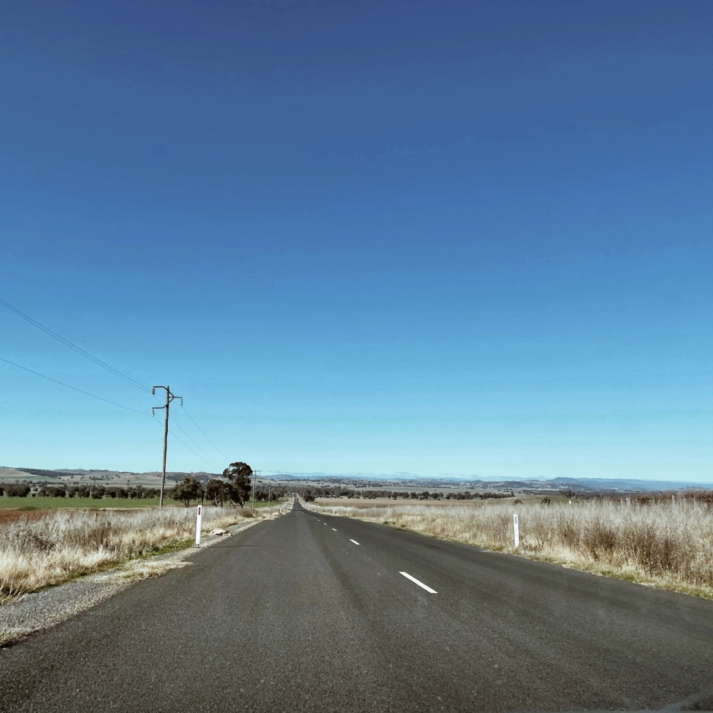 Looking out on a quiet country road flanked by undulating countryside.