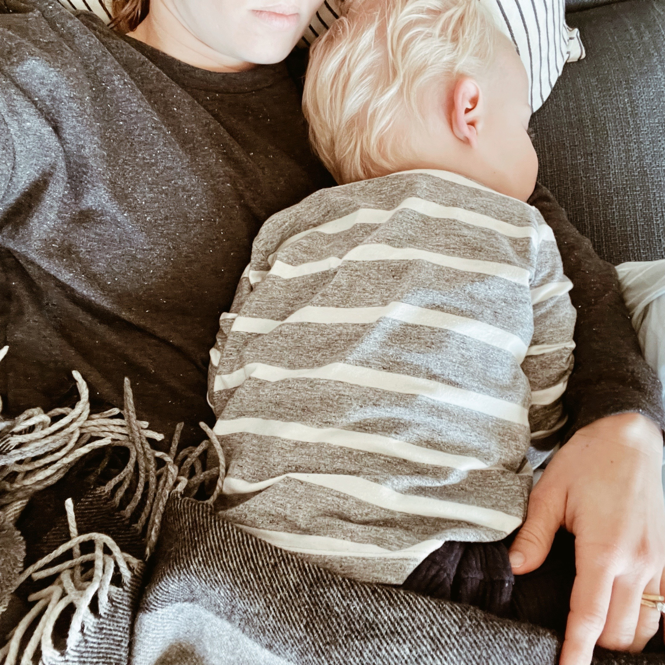 Sleeping toddler boy snuggled up to his mother on a lounge.